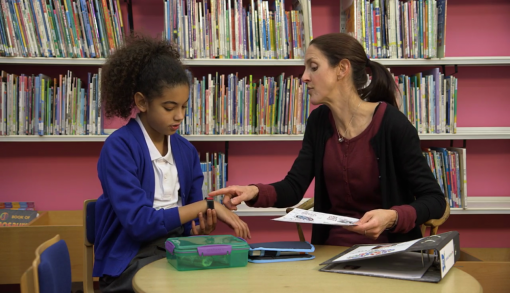A teacher discussing allergies and healthcare plans with a pupil as part of the anaphylaxis and allergy training for schools.