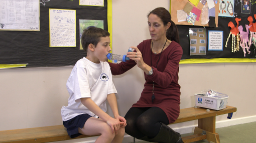 Teacher helps child take his inhaler as part of our Children with Asthma Training Course